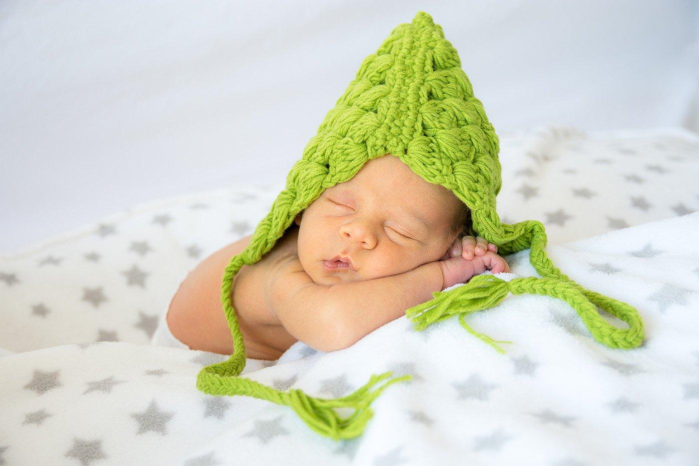 Photo de naissance, bébé avec un bonnet vert dans un drap blanc