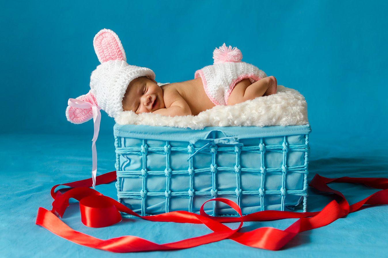 Photo d'un bébé dans un panier, sur fond bleu
